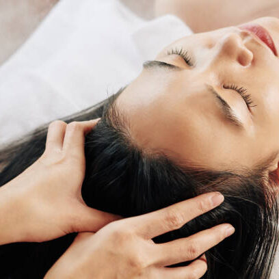 Close-up image of beautician massaging head of female client relaxing on massage bed
